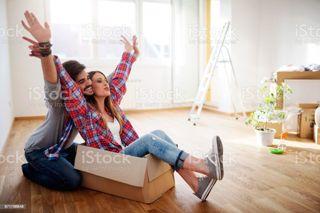 Happy young couple just moved new home unpacking boxes, having fun stock photo