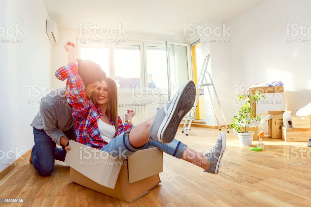 Happy young couple just moved new home unpacking boxes; having fun stock photo