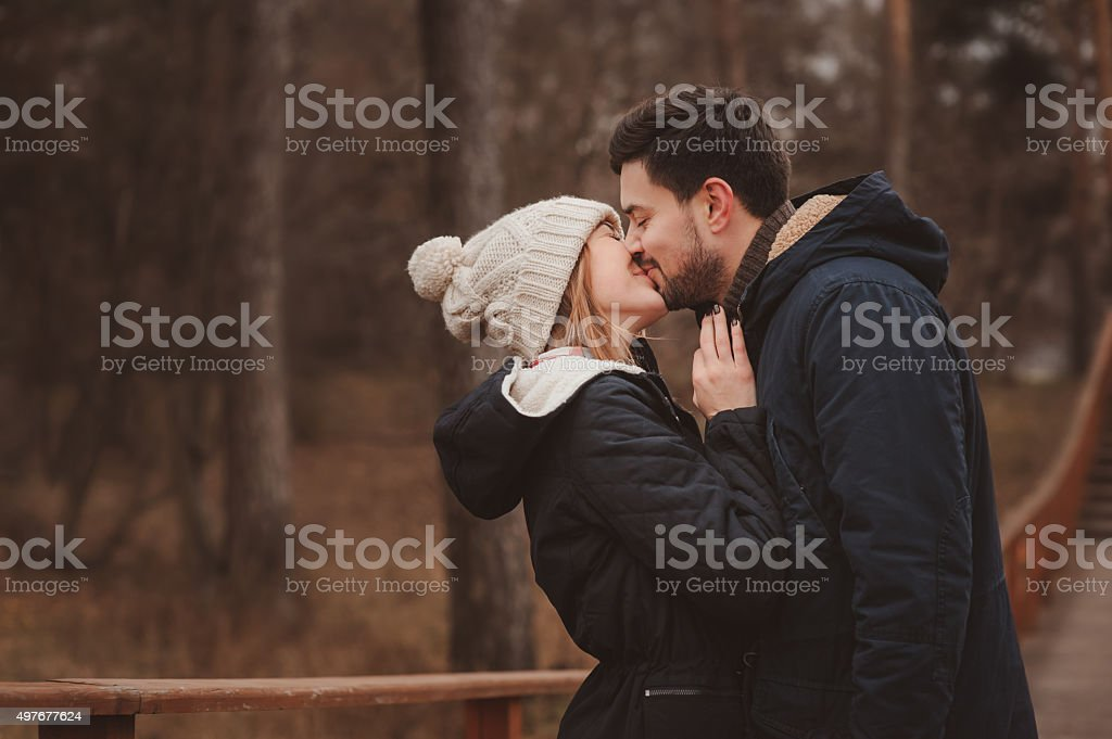 Happy young couple kissing outdoor on cozy warm walk stock photo