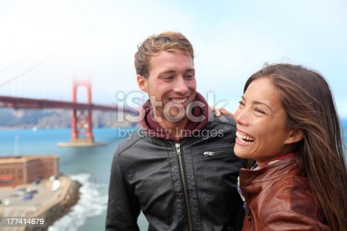 Happy young couple laughing in San Francisco by Golden Gate Bridge. Interracial young modern couple, Asian woman, Caucasian man. Click on the banners for more: