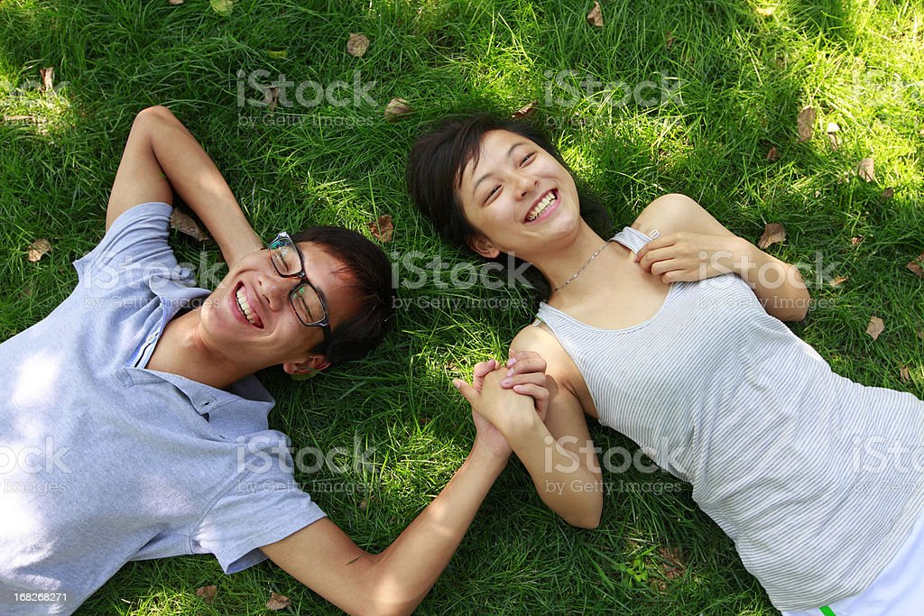happy young couple laying on grass royalty-free stock photo