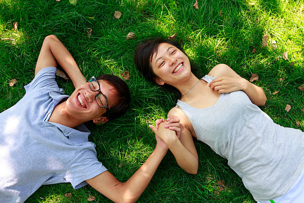 happy young couple laying on grass stock photo
