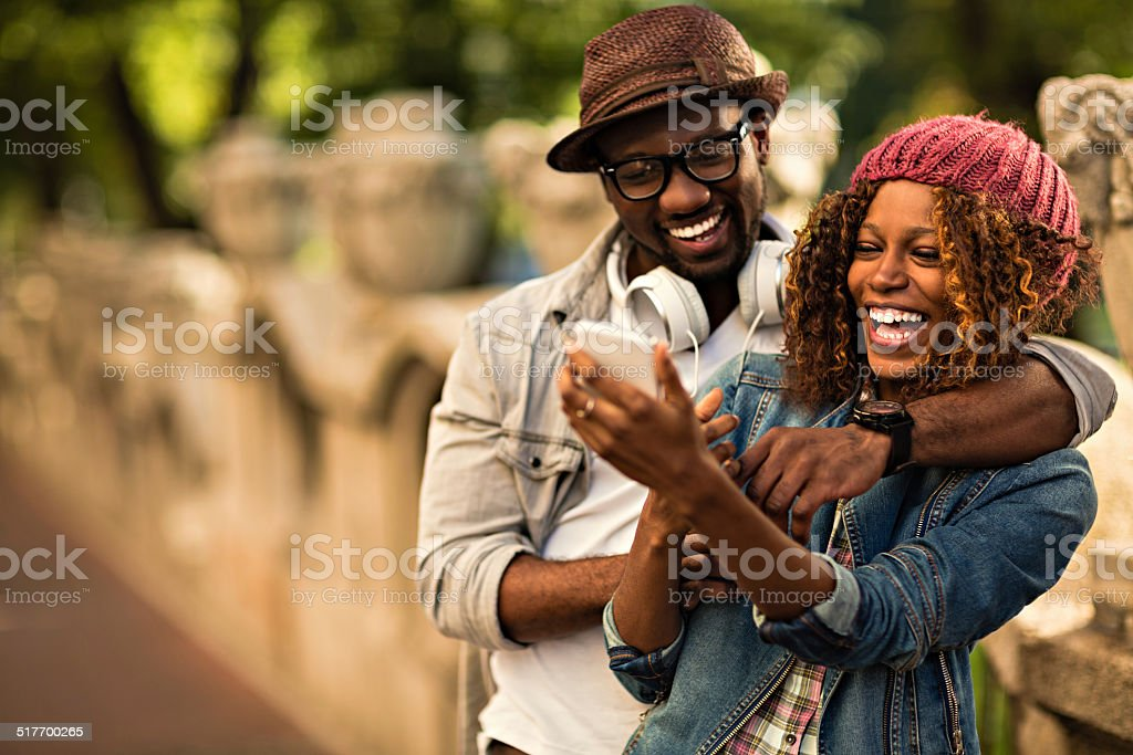 Happy young couple looking at mobile phone royalty-free stock photo