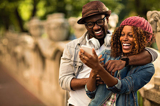 Happy young couple looking at mobile phone stock photo