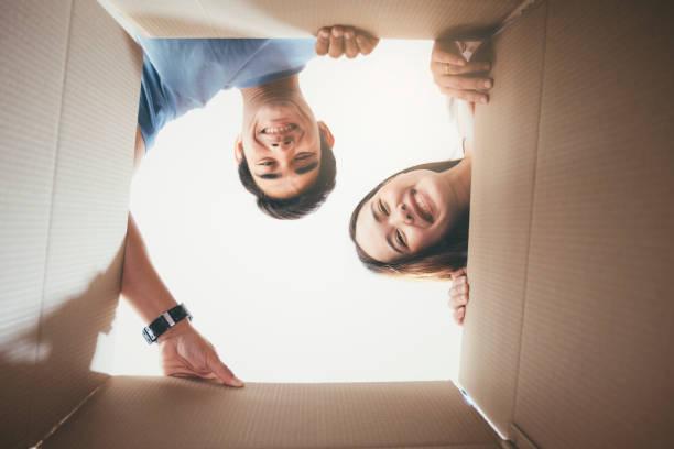 Glückliches junges Paar schaut in die Box – Foto