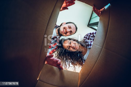 Happy young caucasian couple looking inside the cardboard box.