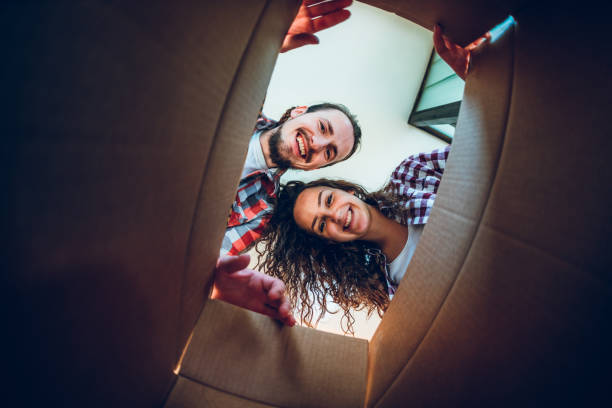 happy young couple looking inside the box - being in a relationship with someone is going to require stock photos and pictures
