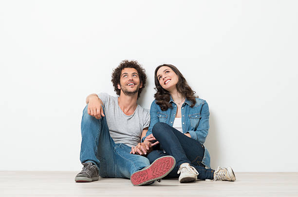 happy young couple looking up - sitting on floor stock photos and pictures