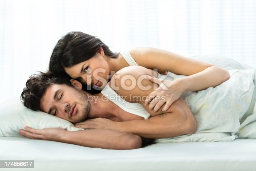 505826794 istock photo Happy young couple lying down in bed 174856617