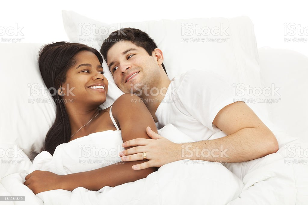 Happy Young Couple Lying in Bed stock photo