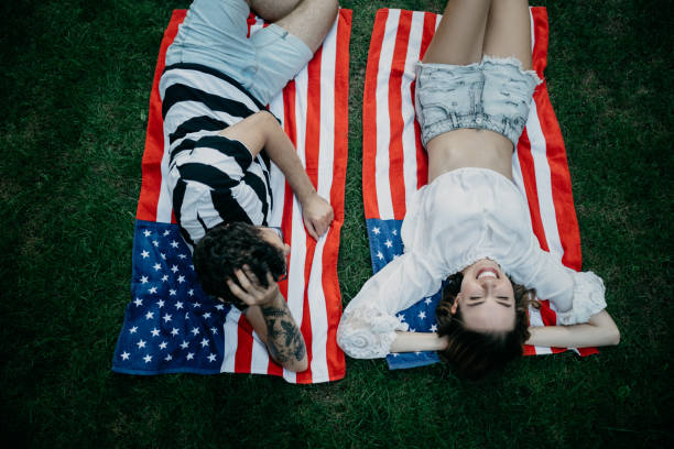 Happy young couple lying on grass Happy young couple lying on grass american flag tattoos for men stock pictures, royalty-free photos & images