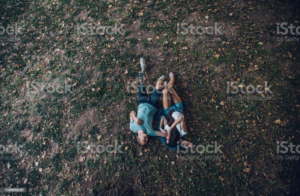 Glückliches junges Paar liegen auf dem Rasen – Foto