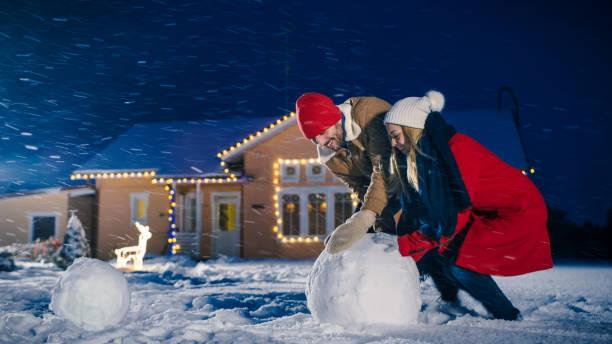 glückliches junges paar macht einen schneemann, beide rollendem großen schneeball. familie spaß an einem winterabend. im hintergrund haus mit girlanden geschmückt. - schneemann bauen stock-fotos und bilder
