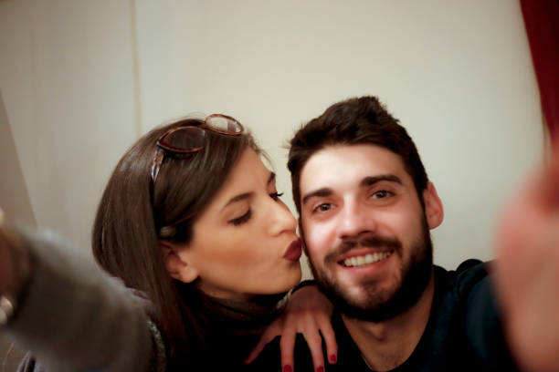 happy young couple makes selfie - brunette woman eyeglasses kiss man foto e immagini stock