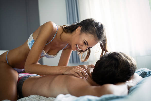 Happy young couple making massage in bedroom stock photo