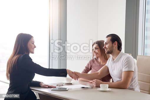 istock Happy young couple making real estate deal, handshake with agent 680437092