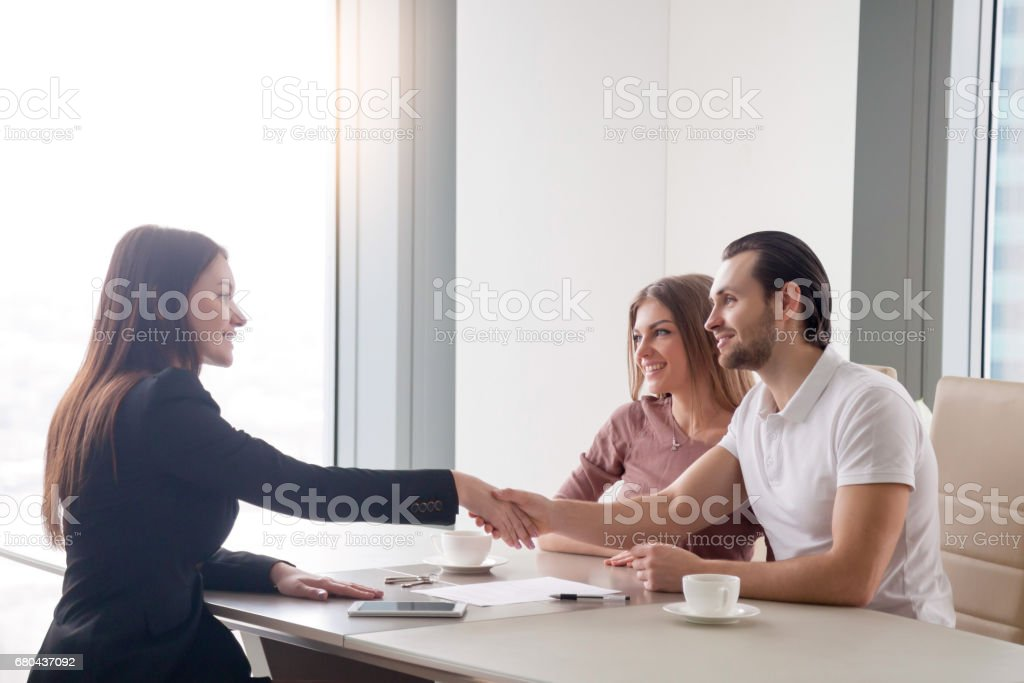 Happy young couple making real estate deal, handshake with agent - Photo
