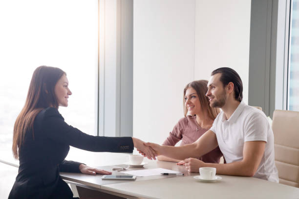 Happy young couple making real estate deal, handshake with agent stock photo