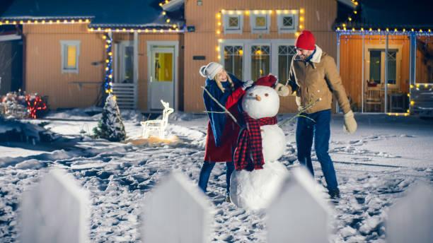 glückliche junge paar machen schneemann im hinterhof ihrer idyllischen haus, während es ist schneefall. sie wickeln sie schneemann mit schal. familie zeit miteinander zu verbringen, an heiligabend. - anzieh nacht stock-fotos und bilder