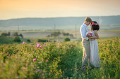 Happy young couple man and woman, adult romantic family. Meet the sunset in a wheat field. Happy smiling. The girl in her hands holds a gift, a bouquet of flowers, from roses