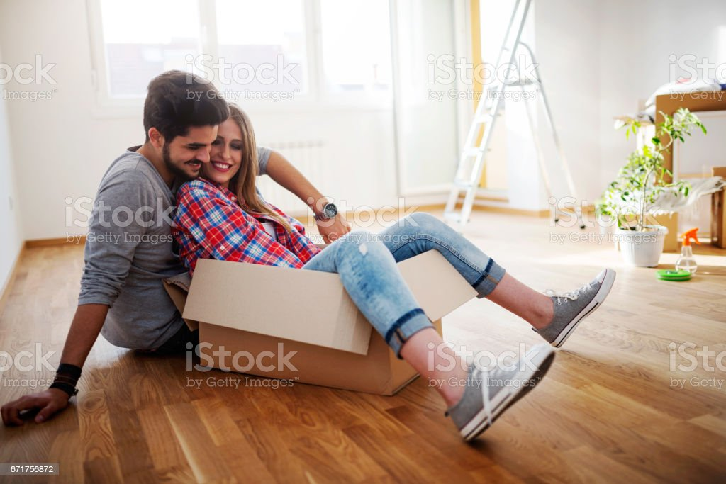 Happy young couple moving in new home unpacking boxes stock photo
