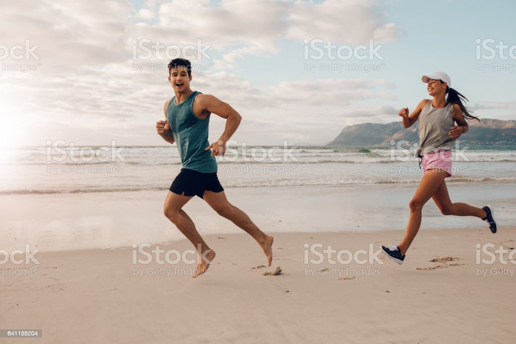 Happy young couple of runners on the beach stock photo