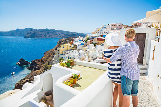 happy young couple on santorini island, greece - santorini stock photos and pictures