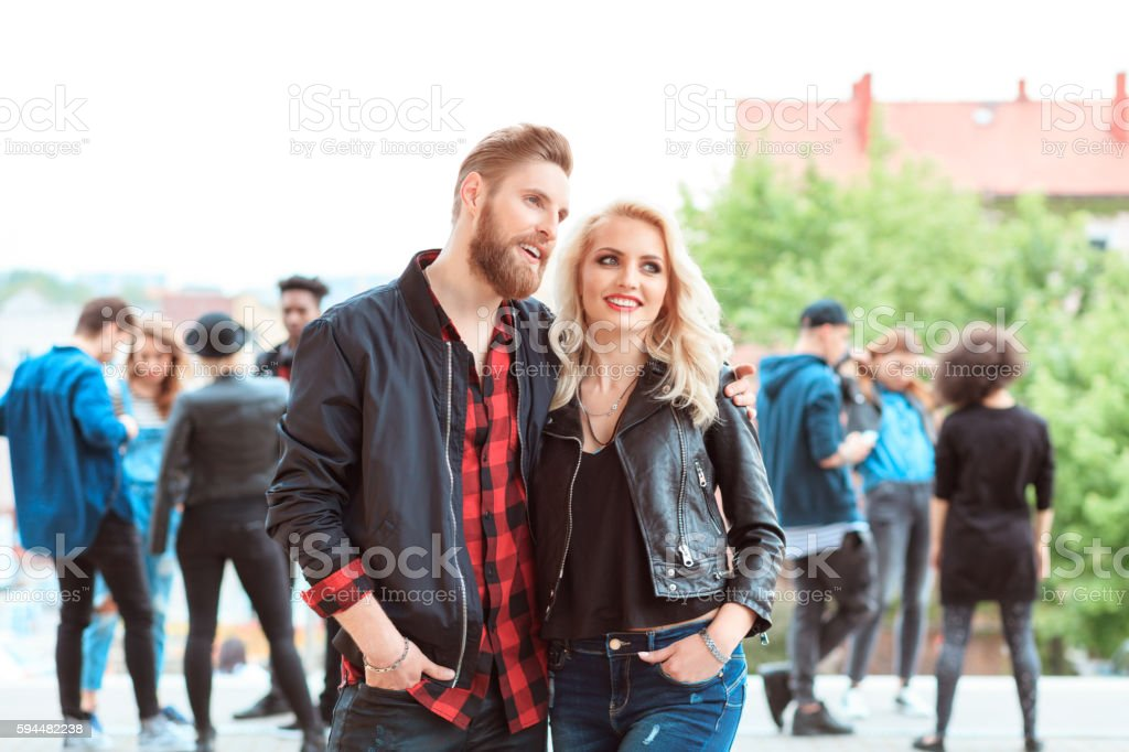 Happy young couple outdoor Bearded young man and beautiful blonde young woman embracing outdoor. Group of people in the background. 20-29 Years Stock Photo