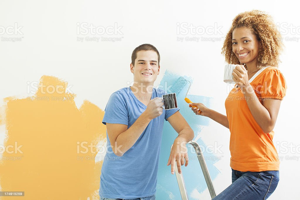 Happy Young Couple Painting the wall. royalty-free stock photo