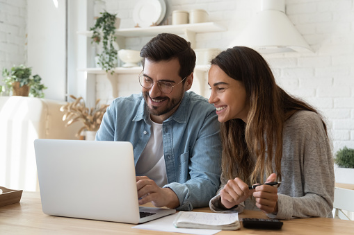 istock Happy young couple paying bills online in computer app 1197547531