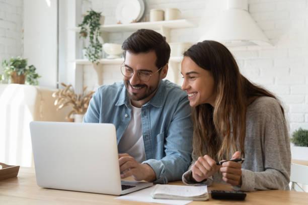 glückliches junges paar bezahlt rechnungen online in computer-app - konsum stock-fotos und bilder