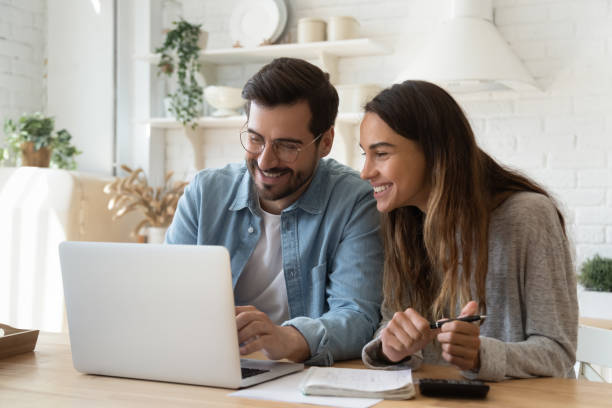 Happy young couple paying bills online in computer app stock photo