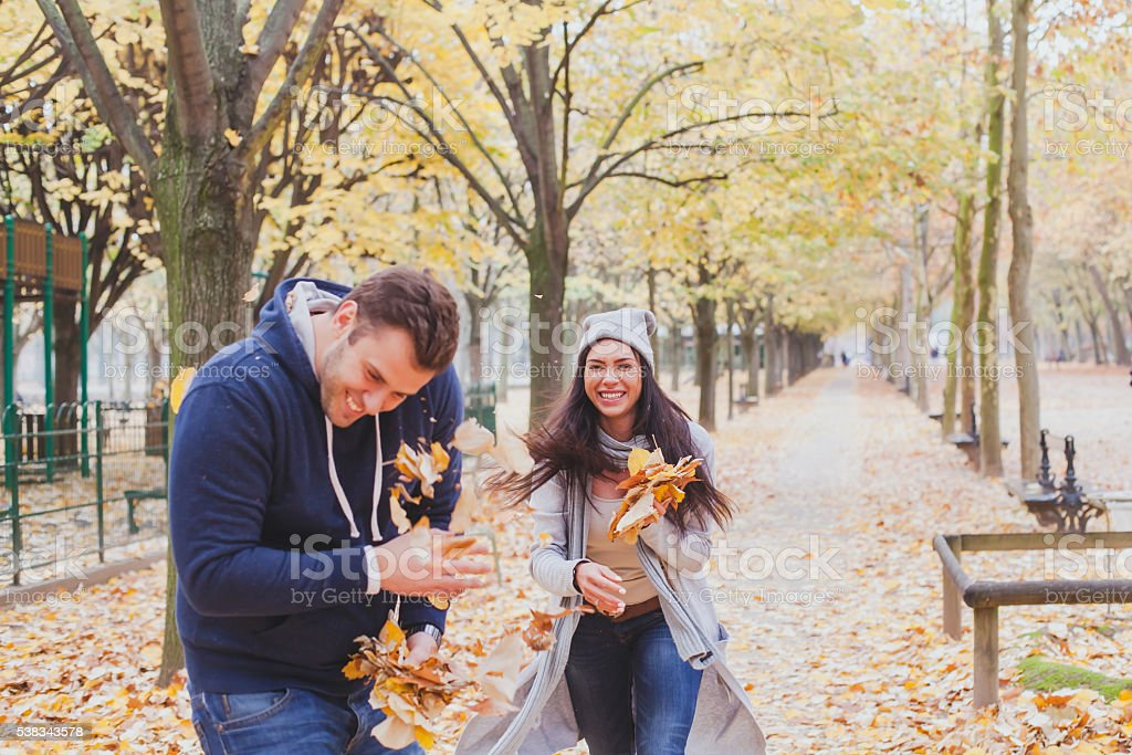 happy young couple playing and laughing together in autumn park