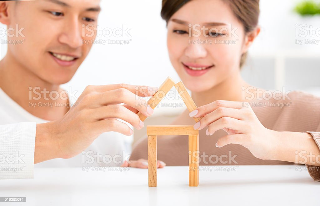 happy young couple playing with toy blocks stock photo