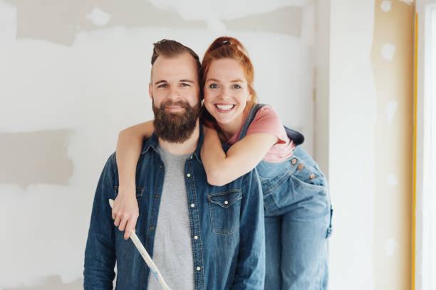 gelukkig jong stel poseren in hun nieuwe huis - mid volwassen koppel stockfoto's en -beelden