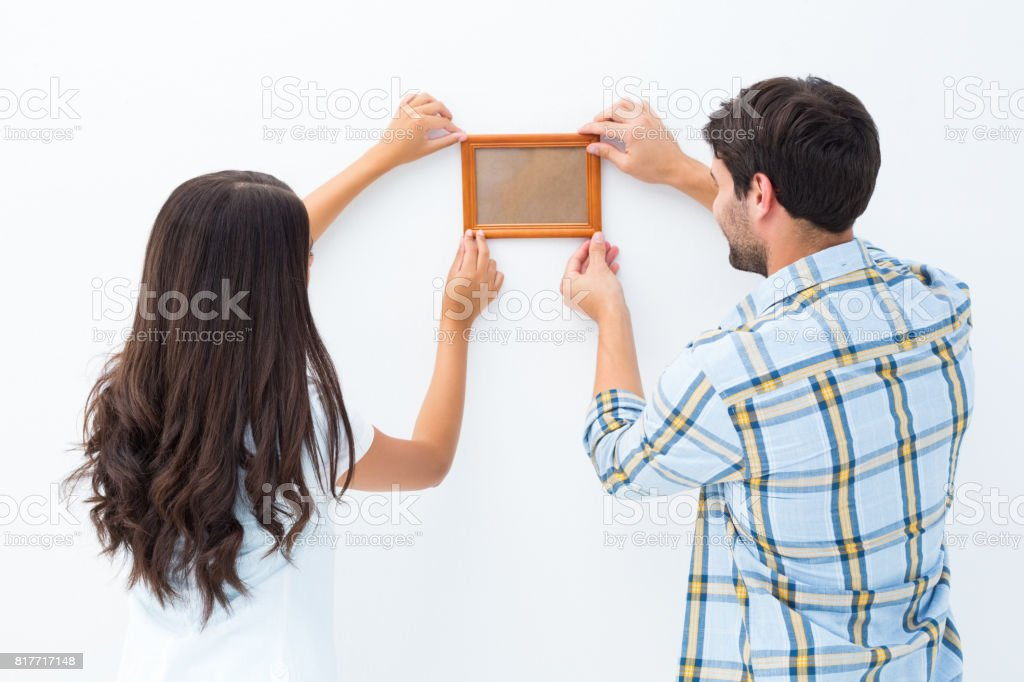 Happy young couple putting up picture frame stock photo