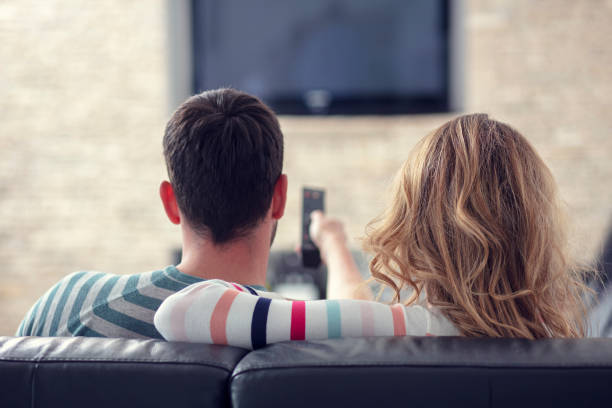 Happy young couple relaxing and watching TV at home. stock photo
