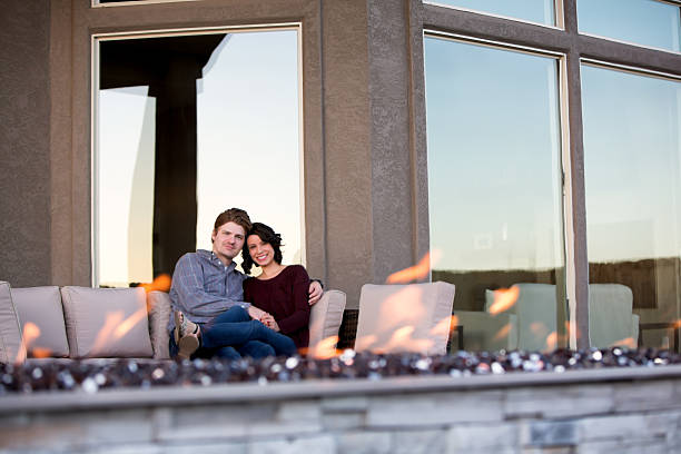 Happy Young Couple Relaxing in Back Yard with Firepit stock photo