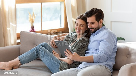 Happy young couple relaxing on cozy couch, using computer tablet together, smiling beautiful woman and man hugging, looking at device screen, watching movie or video, shopping online, browsing apps