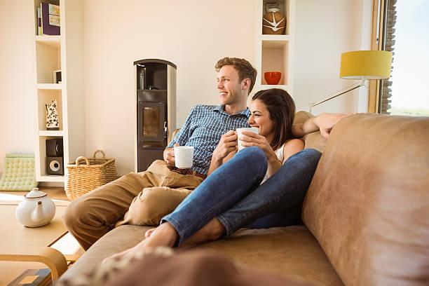 heureux jeune couple de détente sur le canapé-lit - tasse flat photos et images de collection