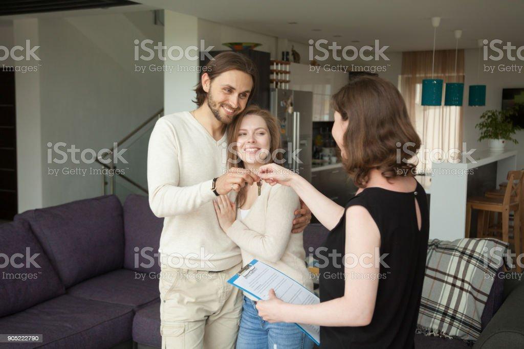 Jóvenes felices pareja inquilinos obtener claves del nuevo alquiler casa - foto de stock