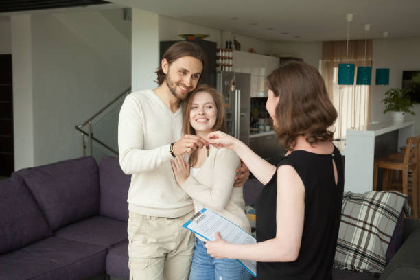 happy young couple renters getting keys of new rental home - tenant stock photos and pictures