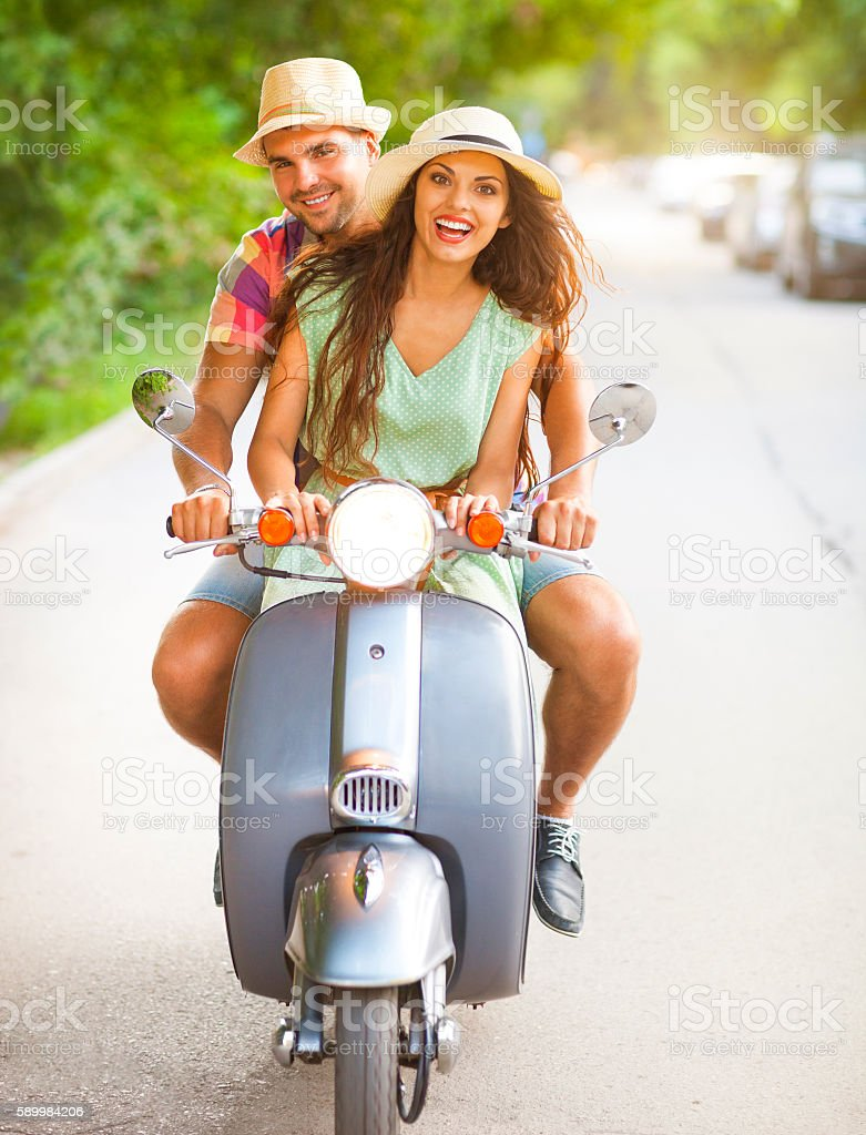 Happy young couple riding a vintage scooter in the street stock photo
