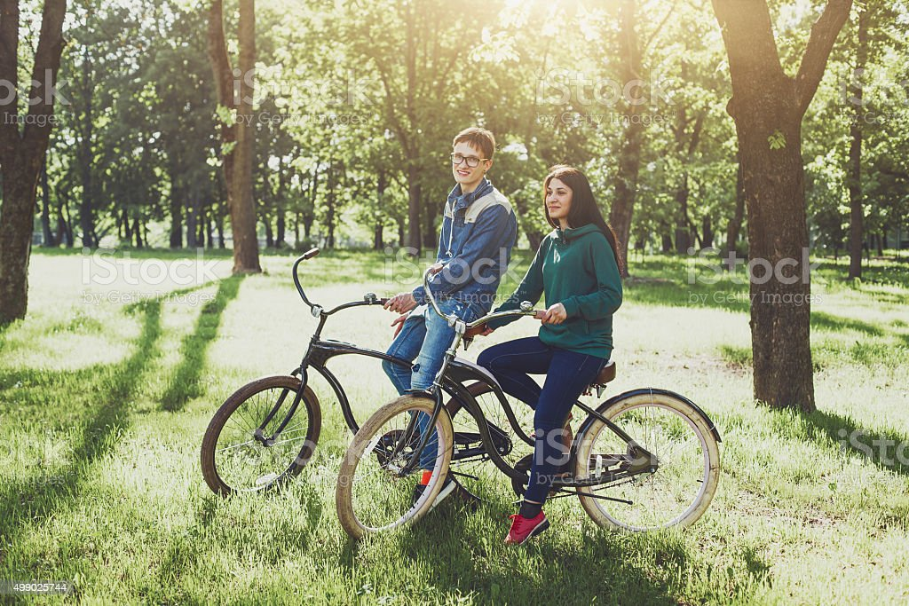 Happy young couple riding bicycles stock photo
