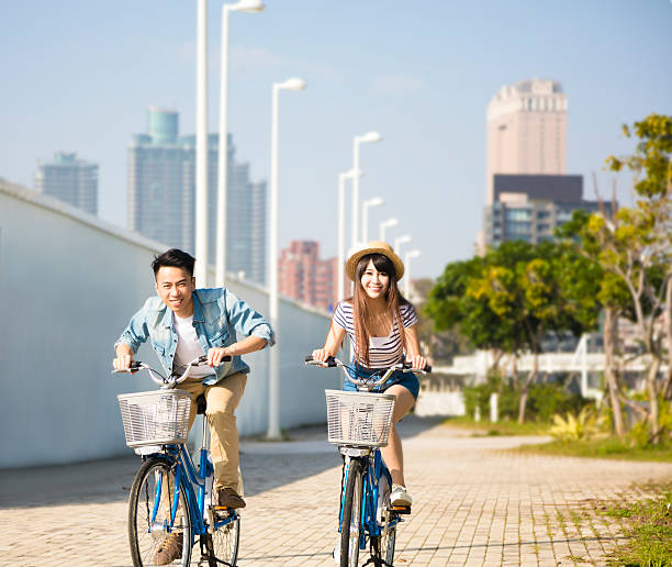 happy young couple riding on bicycle in city park stock photo