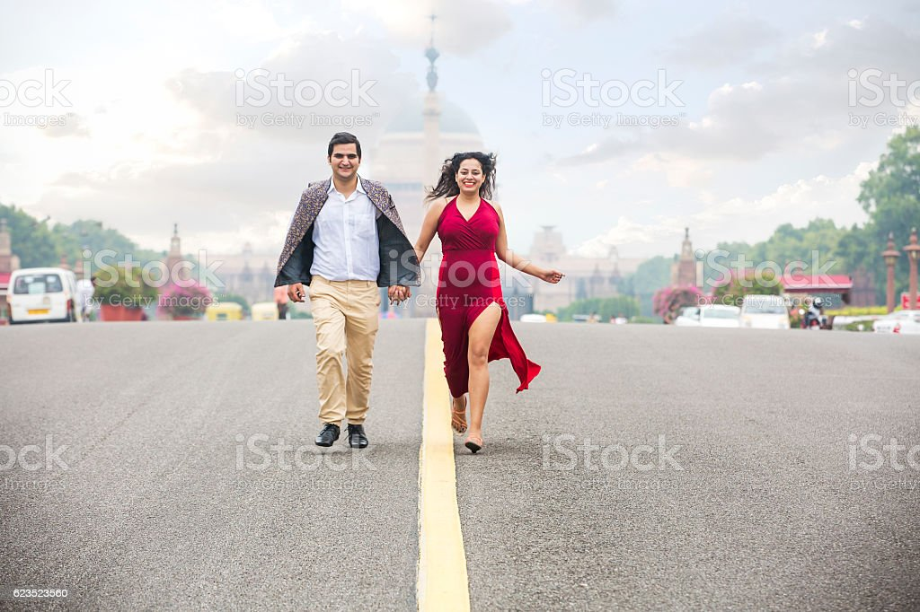 Happy Young couple, running on the road holding their hands stock photo