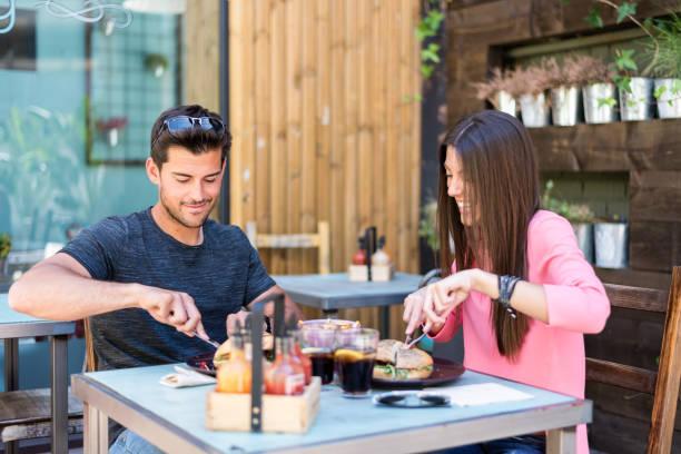 feliz pareja joven sentarse en una terraza restaurante comiendo una hamburguesa - couple lunch outdoors fotografías e imágenes de stock