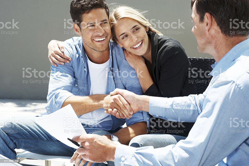 Happy young couple shaking hand with advisor royalty-free stock photo