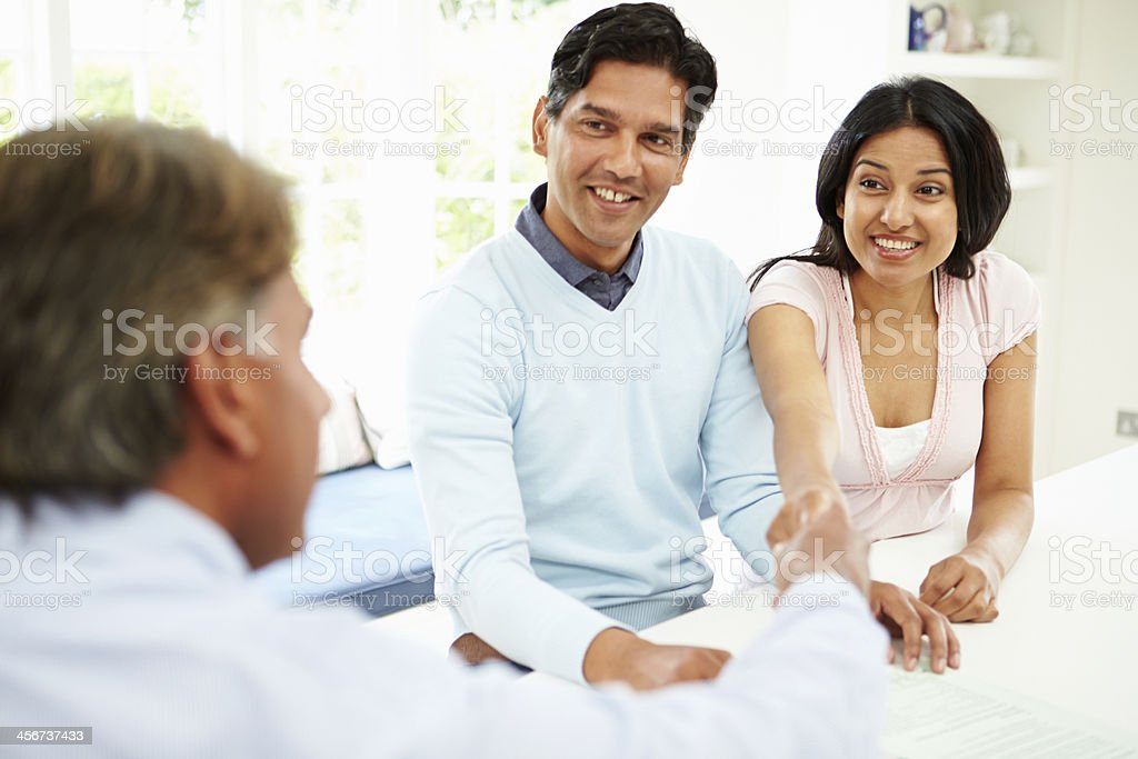 Happy young couple shaking hands with an businessman stock photo