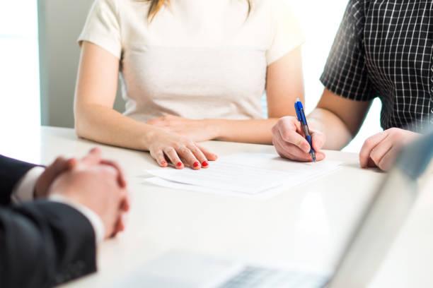 gelukkige jonge paar ondertekening van de overeenkomst of contract. ziektekostenverzekering document, banklening, hypotheek of appartement verhuur papier. - notaris stockfoto's en -beelden